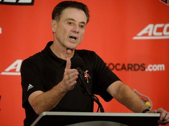 Louisville Cardinals head coach Rick Pitino talks to