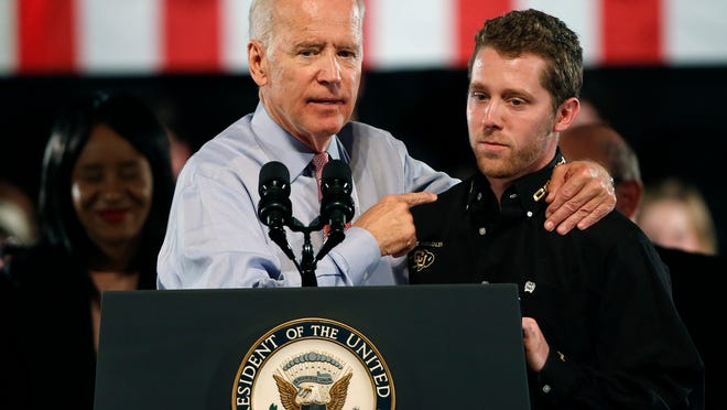 Vice President Joe Biden, left, stands with University of Colorado senior Max Demby, Biden honoring Demby for intervening to stop a sexual assault, on April 8, 2016.