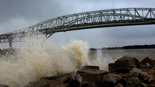 Large waves crash against the seawall at International Flag Plaza in Port Huron.