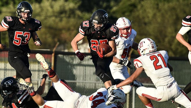 Pleasant's Bryce Lowry leaps to avoid tacklers as he carries the ball downfield against Pandora-Gilboa last season.