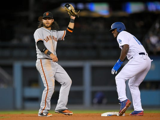 San Francisco Giants shortstop Brandon Crawford, left, holds up his glove after tagging out Los Angeles Dodgers' Yasiel Puig to end the baseball game as Puig tried to steal second during the ninth inning, Saturday, Sept. 23, 2017, in Los Angeles. (AP Photo/Mark J. Terrill)