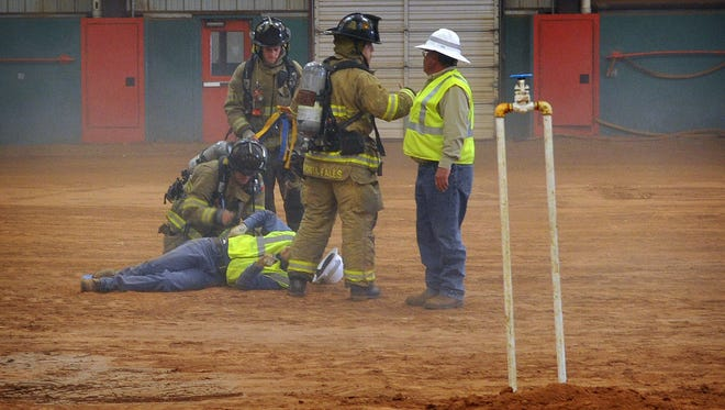 """First Responders treat a """"victim"""" during a demonstration of a mock gas line strike during excavation. The scene played out at the Bridwell Ag Center for a wide variety of service professionals including telecom, natural gas, water, electrical and others. The scenario included excavators digging into a natural gas line causing an explosion."""