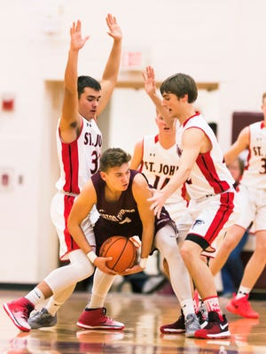 Jacob Osypczuk ,center, of Eaton Rapids is trapped in a double team by Jacob adorn ,left, and Ben Feldpausch ,right, of St.Johns during their season opening game Tuesday December 6, 2016 in Eaton Rapids.