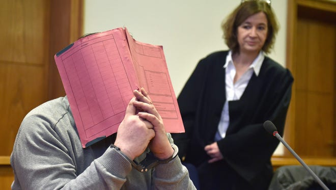 This file photo taken on Feb. 26, 2015 shows German former male nurse known as Niels H. hiding his face behind a folder as he waits next to his lawyer Ulrike Baumann before the start of a hearing during his trial at court in Oldenburg, northwestern Germany.
