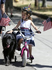 Meredith Heyen, 5, pets her dog Stitch during the Court-Chemeketa Fourth of July Kids Parade on Saturday, July 4, 2015.