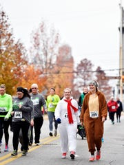 Race participants make their way up Beaver Street in the 20th annual Turkey Trot 5K race hosted by the YMCA of York and York County Thursday, Nov. 24, 2016, in York. The race featured more than 5,100 participants.