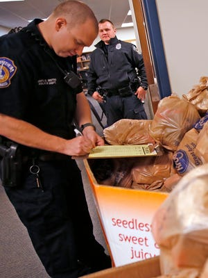 IMPD Officer Jeremy Torres signs out a CARE bag to keep in his vehicle to give to citizens who are in need, Thursday, March 16, 2017.  IMPD and Gleaners are teaming up on a pilot project to expand its mobile pantries to include providing food bags to families in need. Police cruisers responding to calls on the Eastside will carry bags of shelf-stable food to distribute as needed, enough to provide up to 15 meals.  The program officially starts Monday, March 20, 2017.