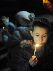 Pinny Cunin, 5, holds a candle during the celebration.