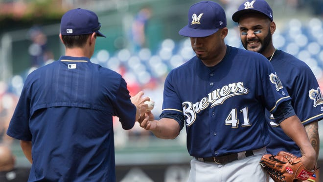Brewers starter Junior Guerra hands the ball to manager Craig Counsell  as he is relieved during the fifth inning Sunday against the Phillies.