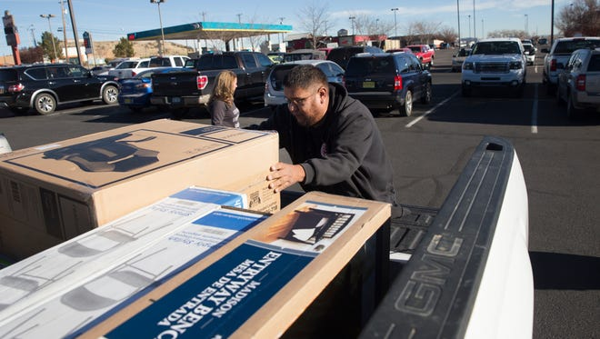 Shopper Loren Harrison loads his purchases into his vehicle Friday at the Four Corners Marketplace in Farmington.