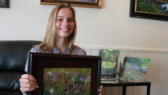 Ava Obert, 12, holds up one of her most recent works completed during a plein air competition at the White River in May. The painting is among the few for sale at Rivertown Gallery in Mountain Home.