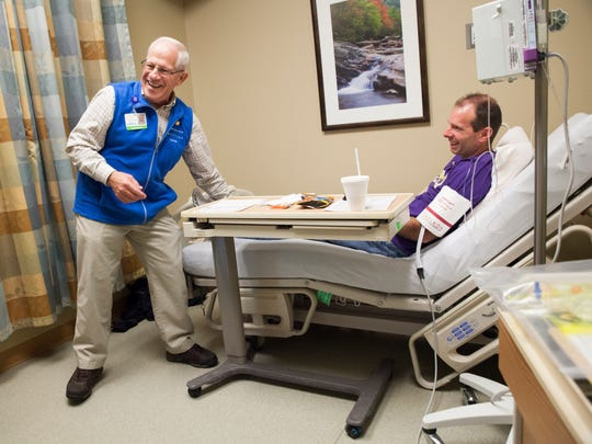 Waiting for his chemotherapy treatment to begin, Mike Ruckman, right, who is battling stage IV colon cancer, laughs with Bill Stover, a volunteer at the RMH Hahn Cancer Center in Harrisonburg on Nov. 13.