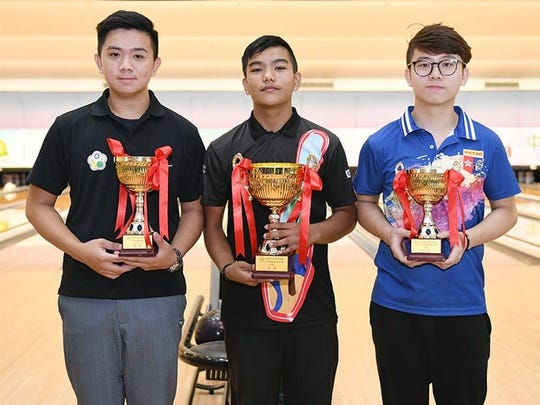Jeremiah Camacho proudly shows off his trophy after winnig the the Youth Masters division of the 2018 Macau China International Open Tenpin Bowling Championships in Macau June 21. At left is Chinese Taipei player Hung Un Tseng and right is Hong Kong player Oscar Poon, who finished second and third, respectively.