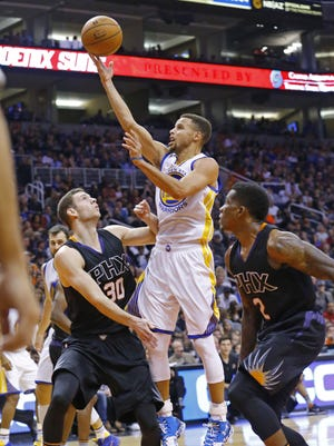 Golden State Warriors guard Stephen Curry (30) shoots  over Phoenix Suns forward Jon Leuer (30) in the second half of their NBA game Friday, Nov. 27, 2015 in Phoenix, Ariz.