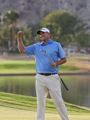 Bill Haas celebrates his victory after rolling in the