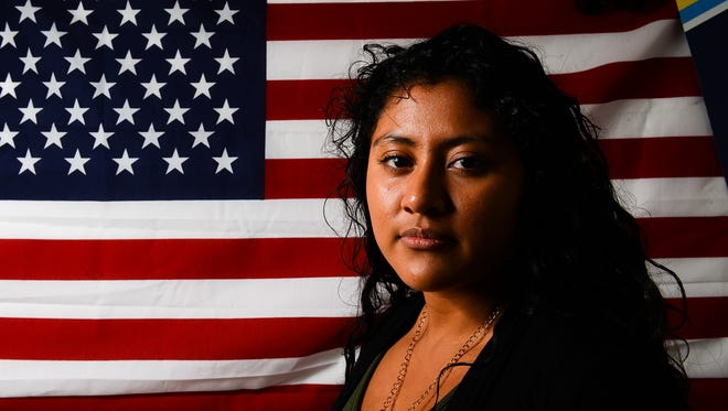 Viviana Alamillo, 23, stands in front of a large American flag that hangs on a wall in her bedroom Wednesday, Oct. 12, 2016, in Lansing. Alamillo immigrated from Mexico to the U.S. at the age of 3 and lived illegally in the U.S. for more than 15 years before she applied for and was granted DACA status.
