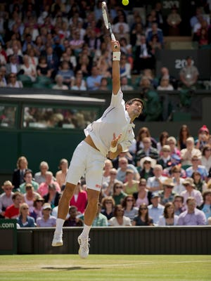 Novak Djokovic leaps for a shot during his third-round match against Gilles Simon at Wimbledon Friday.