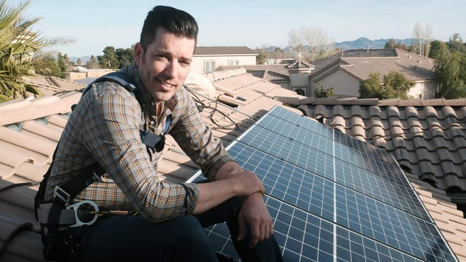 "This image released by Independent Lens shows Jonathan Scott from ""Property Brothers"" installing solar panels on a rooftop in his new documentary ""Jonathan Scott's Power Trip."" The film premieres Monday night as part of Independent Lens on PBS stations across the country."