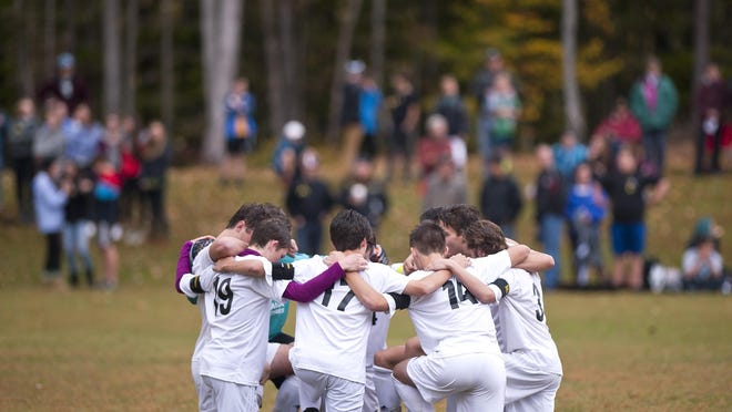 Nine Harwood players huddle on the field before a high school boys soccer game against U-32 in October. It was the Highlanders' first since the death of players Eli Brookens and Cyrus Zschau in a tragic car accident on I-89.