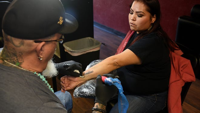 Greg Knuppel, left, works on a tattoo for Marilynn Betselie on Friday at Mr. Tank's Tattoos in downtown Farmington.
