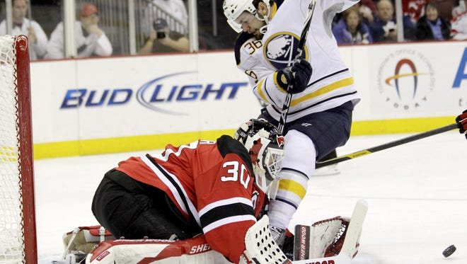 New Jersey Devils' Martin Brodeur (30) stops a shot by Buffalo Sabres' Patrick Kaleta (36) during the first period of an NHL hockey game in 2012.