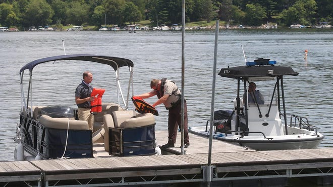 Lucas Pace, a Muskingum Watershed Conservancy District ranger, performs a mock safety check on the boat of Craig W. Butler, MWCD executive director, on Atwood Lake.
