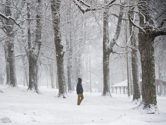 A student hurries across a snowy Farquhar Park in York