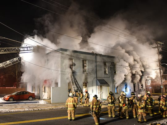 Firefighters battle a fire at the Mane Street Hair and Tanning Salon as an estimated 50 or more firefighters battled a two-alarm fire at the former First National Bank of Fredericksburg at the corner of Pine Grove and Main streets in Fredericksburg on Tuesday, Dec. 20, 2016.