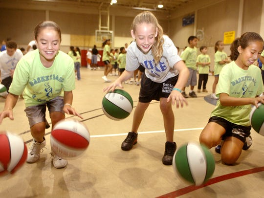 Nicole McGunegle, 11, from left, Alejandra Barraza, 10, and Victoria Foster, 11, practiced dribbling two balls at a time in 2004 at Basketball in the Barrio. More than 100 children participated in the event.