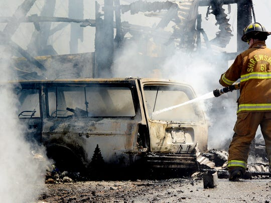 A firefighter douses flames in a vehicle during a fire