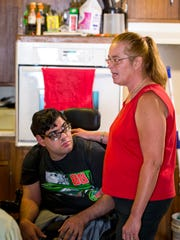 Louis Facenda Jr. with his caregiver Anita McGehee Wednesday, August 30, 2017, at his West Des Moines home.  Louis Facenda Jr.  spent as much as half his day in a dirty diaper this summer, an issue his mother and caregiver insists is a direct result of Iowa Medicaid management's profit motive.