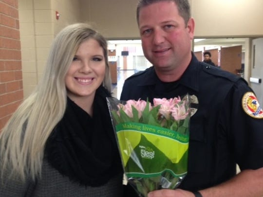 Belmina Medanovic, a senior at Urbandale High, poses with School Resource Officer Matt Flattery. She gave him flowers earlier on Wednesday.
