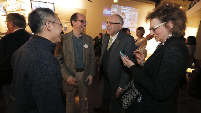 Karl Loewenstein and Kim Nguyen congratulate Stan Mack, superintendent of the Oshkosh Area School District, on the passage of the OASD referendum as Mack's wife Margaret looks at Becket's in Oshkosh.