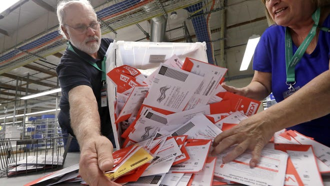 RENTON, Wash. -- Election workers Mark Bezanson, left, and Julie Olson dump ballots collected earlier in the day from drop boxes onto a table for sorting at the King County Elections office in 2018. Voters in Washington state all vote only by mail.