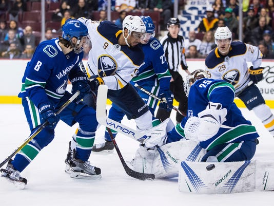 Vancouver Canucks goaltender Jacob Markstrom (25) of Sweden, makes a save as Buffalo Sabres left wing Evander Kane (9) and right wing Jason Pominville (29) look for the puck while Canucks defenseman Christopher Tanev (8) and defenseman Ben Hutton (27) defend during the first period of an NHL hockey game Thursday, Jan. 25, 2018, in Vancouver, British Columbia. (Darryl Dyck/The Canadian Press via AP)