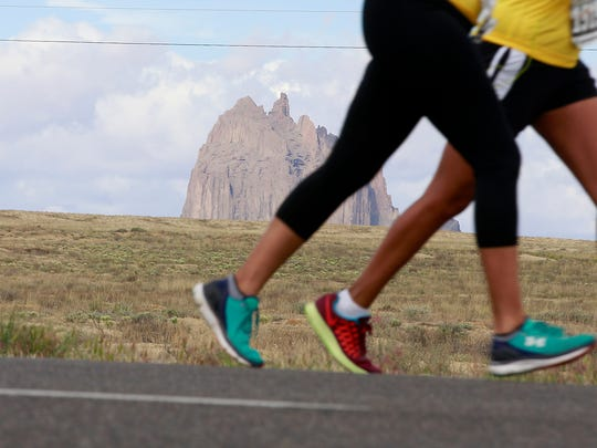 The Shiprock pinnacle looms in the distance as runners take part in the Shiprock Marathon on May 7, 2016.
