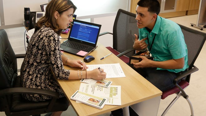Navigator Dianelys Dominguez, left, assists Giovanny Vega, 18, of Miami sign up for health insurance under the Affordable Care Act in November 2014 at the Borinquen Medical Center in Miami.