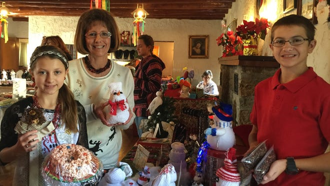 """Holiday crafter Marlene Siepel, Alto, at her table at Carrizozo Holiday Hoedown last Saturday. She is shown with her """"elf"""" assistants, grandchildren Madilyn and Charles Conner from Levelland, Texas. Siepel is a line dance instructor at Capitan Senior Citizens Center."""