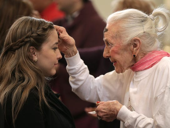 In this 2016 file photo, Doris Gurss, a Eucharist minister at St. Patrick Cathedral, applies ashes to the foreheads of parishioners on Ash Wednesday.