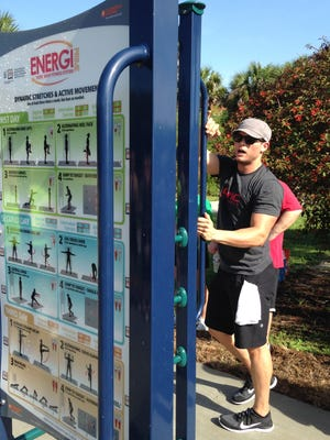 Personal trainer and exercise physiologist Michael Stull tries out the new fitness station at Lakes Park.