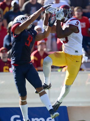 Oct 15, 2016; Tucson, AZ, USA; Trojans wide receiver JuJu Smith-Schuster (9) makes a catch as Wildcats cornerback Dane Cruikshank (9) defends during the second half at Arizona Stadium. The Trojans won 48-14.