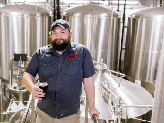 """John Stewart, director of brewing operations, poses for a portrait on the brew deck with a glass of Perrin Brewing Company's most popular year-round beer, Perrin Black, in Comstock Park, Mich. on Thursday, Feb. 23, 2017.  According to Stewart, Perrin Black is known for its """"easy drinking""""."""