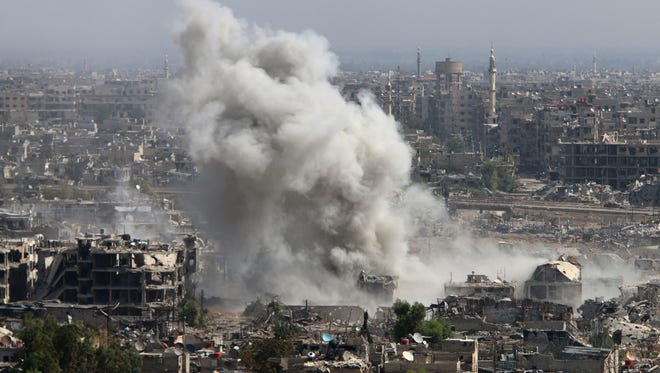 In this photo taken on Wednesday, Oct. 14, smoke rises after shelling by Syrian army in Jobar, Damascus, Syria.
