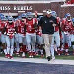 Ole Miss coach Hugh Freeze leads the Rebels onto the field before a game against Vanderbilt last season.
