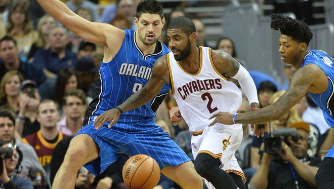 Cleveland Cavaliers guard Kyrie Irving (2) dribbles the ball between Orlando Magic center Nikola Vucevic (9) and guard Elfrid Payton (4) during the first quarter at Quicken Loans Arena.