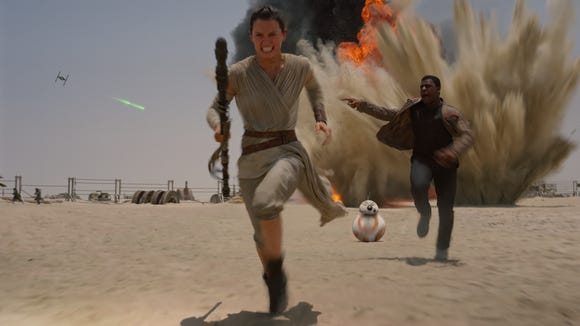 Rey (Daisy Ridley, left), BB-8 and Finn (John Boyega) hightail it in 'Star Wars: The Force Awakens.'