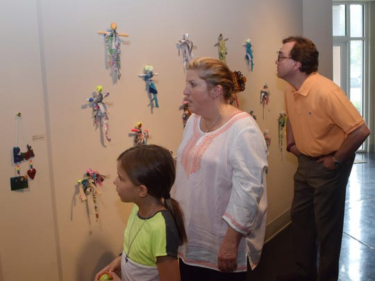 Grace Winstead (left) and her parents Nancy and Zeb Winstead look over artwork created by members River Oaks Art Center's summer camp program.