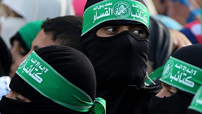 Palestinian fighters of the Ezz Al-Din Al Qassam militia, the military wing of Hamas, attend a rally to commemorate the 27th anniversary of Hamas militant group in  Gaza City on Dec. 14, 2014.