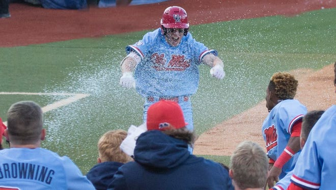 Ole Miss' Henri Lartigue greets his teammates at home plate after hitting a two-run, walk-off home run Saturday against Kentucky.