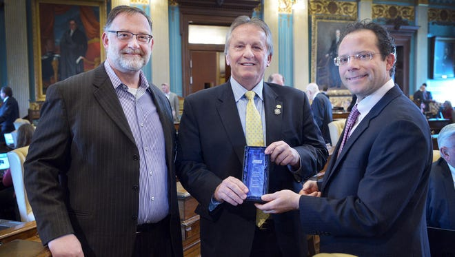 Sen. Mike Nofs, displays the Senator of the Year award with John T. Reurink, left, publisher and co-owner of MIRS, and Kyle Melinn, right, news editor and co-owner of MIRS.